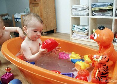 A baby taking a bath with a lot of toys. Courtesy of Greenpeace and Stefan Bungert.