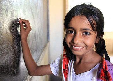 Universal Education is an important and timely international challenge. Photo of a young girl writing on a chalkboard at school. Courtesy of USAID.