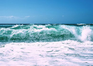 Breaking waves at the beach creating microbubble containing whitewater.